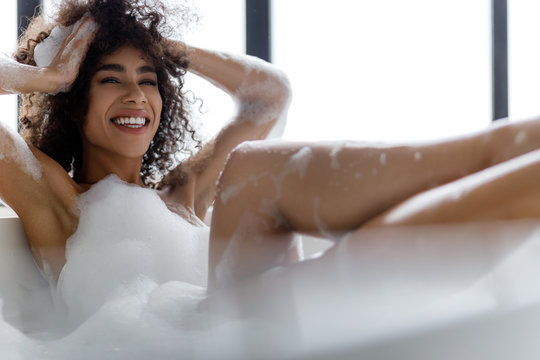 Cheerful Afro American girl relaxing in bathtub