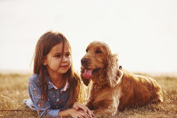 Warm and quiet. Cute little girl have a walk with her dog outdoors at sunny day