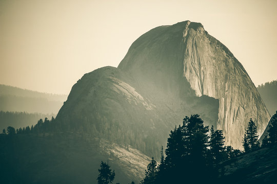 Half dome Yosemite national park cinematic view covered in smoke clouds of wildfires.