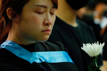 A graduate cries as she paying tribute with flower to Chow Tsz-lok, 22, a university student who fell during protests at the weekend and died early on Friday morning, at the Hong Kong University of Science and Technology, in Hong Kong