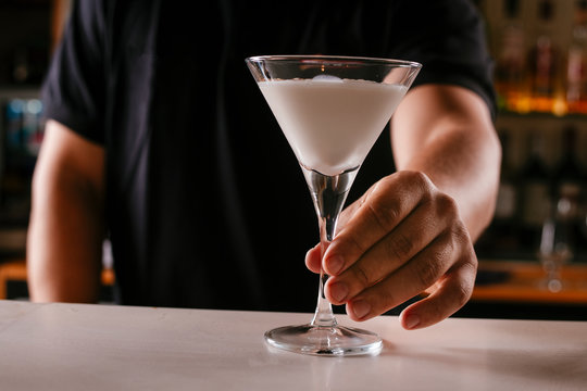 Close up of bartender serving martini. Cocktail based on milk and coffee.