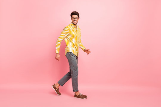 Full length profile photo of handsome guy going down street abroad exploring historic buildings wear specs stylish striped shirt pants isolated pink color background
