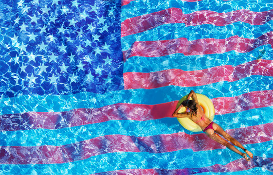 Woman swimming in the pool with USA flag on bottom