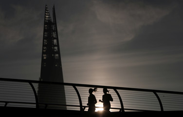 People jog across Millennium Bridge as the sun rises behind the Shard in London