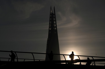 Commuters walk across Millennium Bridge as the sun rises behind the Shard in London