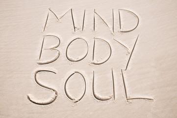 Holistic health message handwritten in smooth sand spelling out Mind Body and Soul on the beach