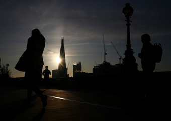 Commuters walk past the Shard at sunrise in London