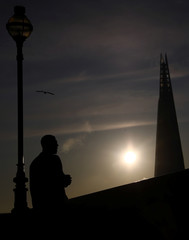 A man watches the sun rise behind the Shard in London