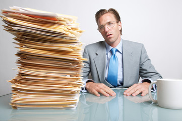 Businessman looking overwhelmed by the stack of paperwork on his desk