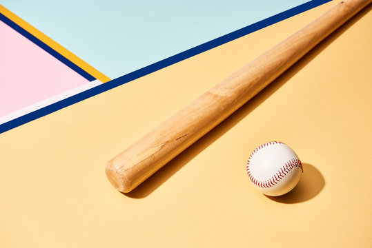 Wooden baseball bat and ball on colorful background with lines