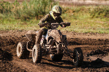 Motocross quad race with races who are covered with mud in an old motocross track.