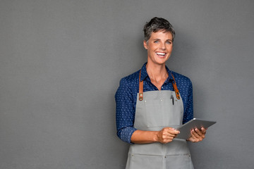 Mature woman in apron holding digital tablet