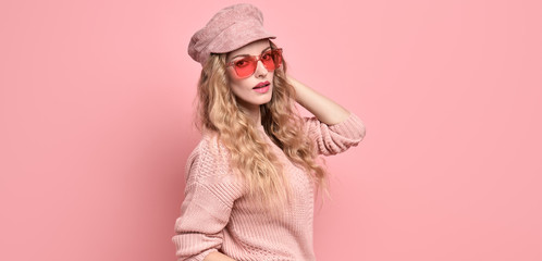 Wall Mural - Fashionable lovable woman in Trendy pink outfit, stylish hairstyle, makeup smiling. Young blonde in jumper. Sensual beautiful model girl in stylish sunglasses, pastel fashion beauty concept on pink