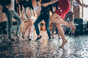 Cropped closeup photo of slim perfect legs girls guys meeting rejoicing dance floor x-mas party glitter flying wear formalwear red dress silver skirt pants restaurant indoors