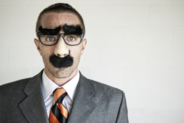 Businessman hiding his identity wearing a disguise of glasses with thick eyebrows and mustache looking at camera with blank expression