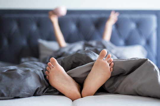 good morning concept - female hands and legs sticking out from the blanket