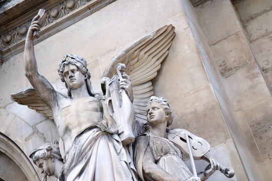 """Stone statues of violinist, flutist, and winged lute player, """"Instrumental Music,"""" by Jean-Baptiste Claude Eugène Guillaume outside the Opera Garnier, in Paris, France"""