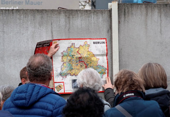 People watch a map of the divided West and East Berlin shown on remains of the Berlin Wall at the Wall memorial on Bernauer Strasse in Berlin