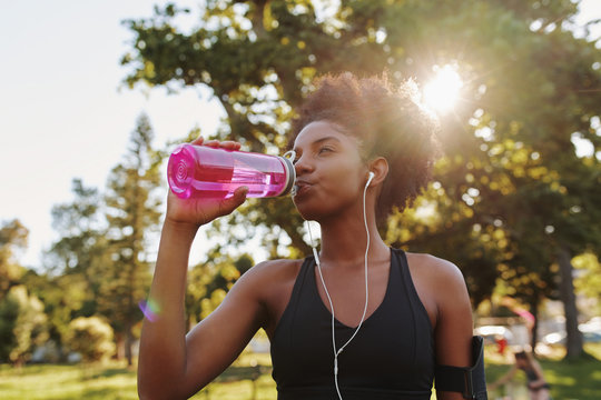 Fitness athlete young african american woman listening to music on earphones drinking water in a reusable water bottle after working out exercising on sunny day at the park