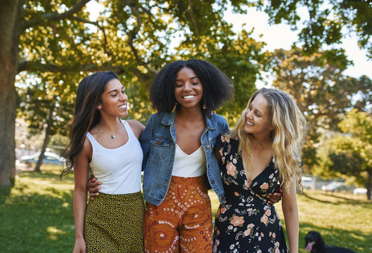 Portrait of a group of happy three diverse young women hugging laughing and having fun in the park on a sunny day while walking