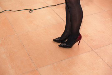 on the floor are beautiful slender female legs, dressed in black tights and shod in black shoes. Cable routing from the microphone. The concept of a person speaking to the public, women.