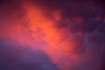 Unusual pink-purple mammatus clouds at sunset. Blurred image for backgrounds.