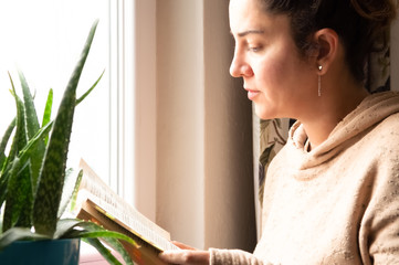 Beautiful Caucasian woman reading a book by the window on her leisure time