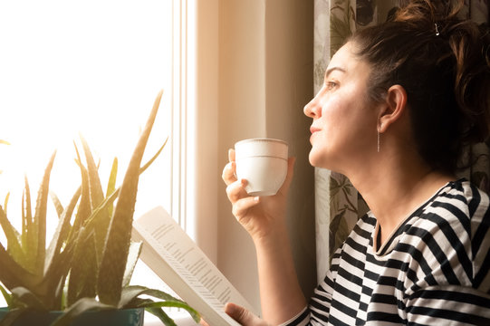 Adult Caucasian woman sitting near window at home relaxing in her living room reading book and drinking coffee or tea