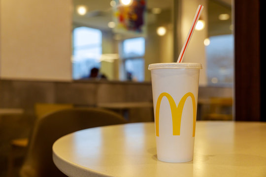 Cup of McDonald's Cola in the background of the McDonald's restaurant. McDonald's Corporation is the restaurants.