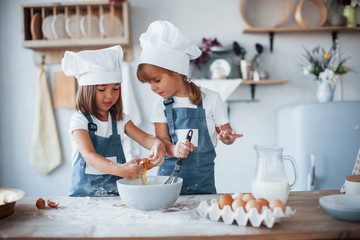 Family kids in white chef uniform preparing food on the kitchen