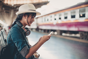 Asian tourist teenage girl at train station using smartphone map, social media check-in, or buy ticket booking. Modern travel app technology, lone traveler, Summer vacation railroad adventure concept