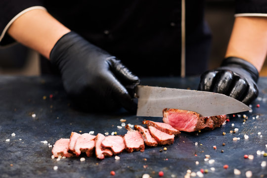 Culinary master class. Striploin steak. Closeup of chef hands slicing medium rare grilled beef meat.