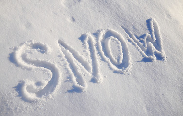 The words SNOW are written in snow. Written word on a snow white field.