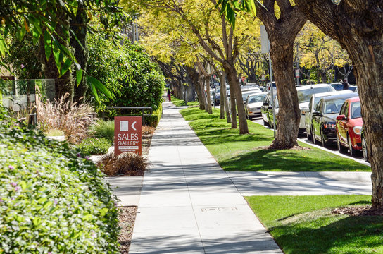 Los Angeles, USA - March 9, 2014: Sidewalk on street in downtown LA in Beverly Hills with residential houses and trees with sales gallery sign