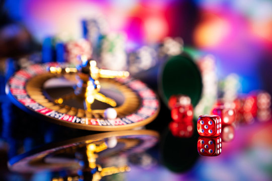 Casino theme.  Gambling games. Roulette, dice and poker chips on a colorful bokeh background.