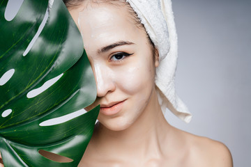 An Asian woman in a towel on her head covered half her face with a sheet of monstera, her shoulders are bare