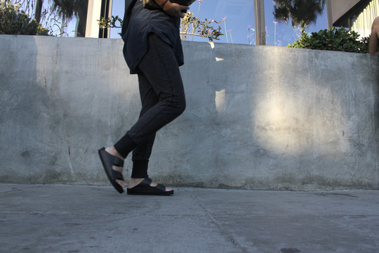 woman in black walking down sidewalk in sandals