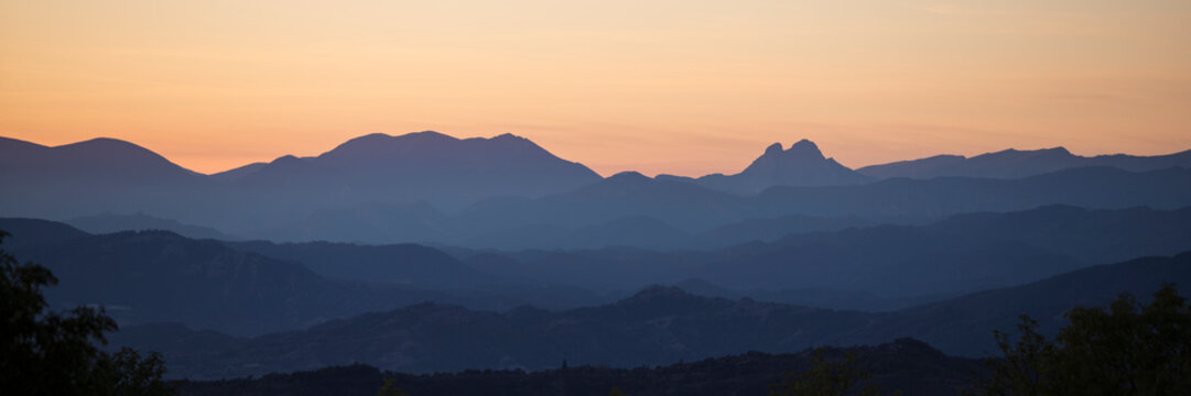 Panoramic silhouette of mountains against an orange sky.