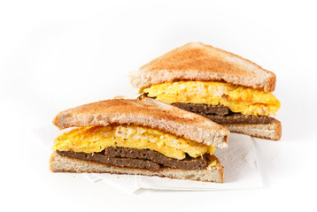 Sausage, egg and cheese breakfast sandwich on a white background