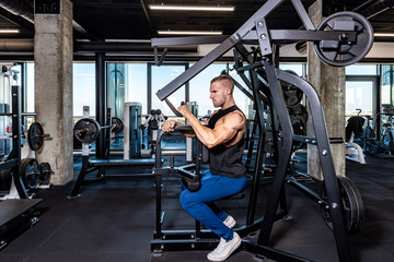 Young sweaty strong muscular fit man back muscles workout training with weights on the machine in the gym