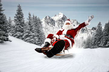 Red Santa Claus riding a wooden sled. An older man with a beard delivers presents to a child. Winter mountains landscape and snow-covered trees with frost. Fir branches, winter time. Christmas spells