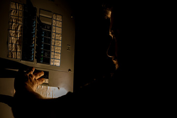 Man Checks Home Fuse Box in a Dark Power Outage