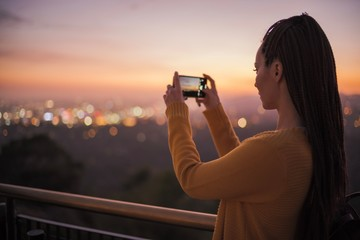 Woman taking picture of a modern city