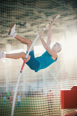 Pole vaulting indoors - young fit man jumping leaning on the pole - sport stadium