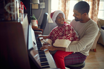 Happy African American father with child girl on Christmas play music on piano.