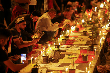 Demonstrators read Quran and light up candles for the people killed at an anti-government protest in Iraq, in Baghdad