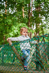 baby girl climbing on a rope playground