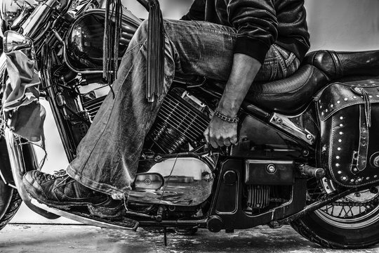biker starting a motorcycle in black and white