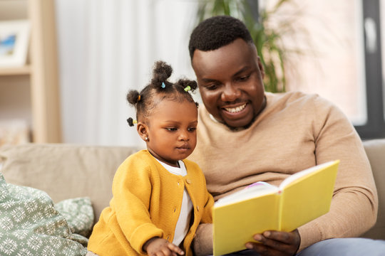 family, fatherhood and people concept - happy african american father reading book for baby daughter at home