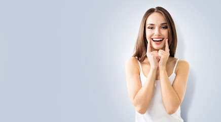 Happy woman pointing toothy smile. Portrait of optimistic lovely brunette girl. Grey color background with copy space, for some advertising text or slogan. Optimism or Dental Health Care concept.